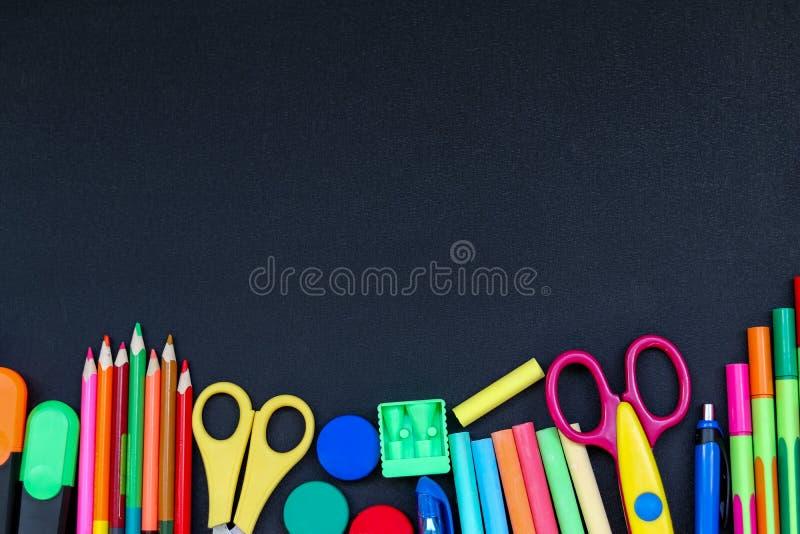 Φωτεινές σχολικές προμήθειες στο υπόβαθρο πινάκων έτοιμο για το σχέδιό σας στοκ φωτογραφία