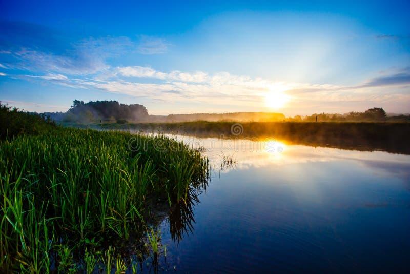 Φωτεινή ανατολή και μπλε ουρανός πέρα από τον ομιχλώδη ποταμό στοκ φωτογραφία