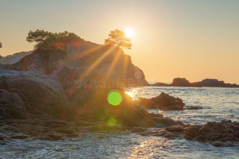 Φωτεινή ανατολή στην παραλία θάλασσας Lloret de Mar Ο ήλιος λάμπει πέρα από το δύσκολο απότομο βράχο στην παραλία Κόστα Μπράβα Ακ στοκ εικόνες με δικαίωμα ελεύθερης χρήσης