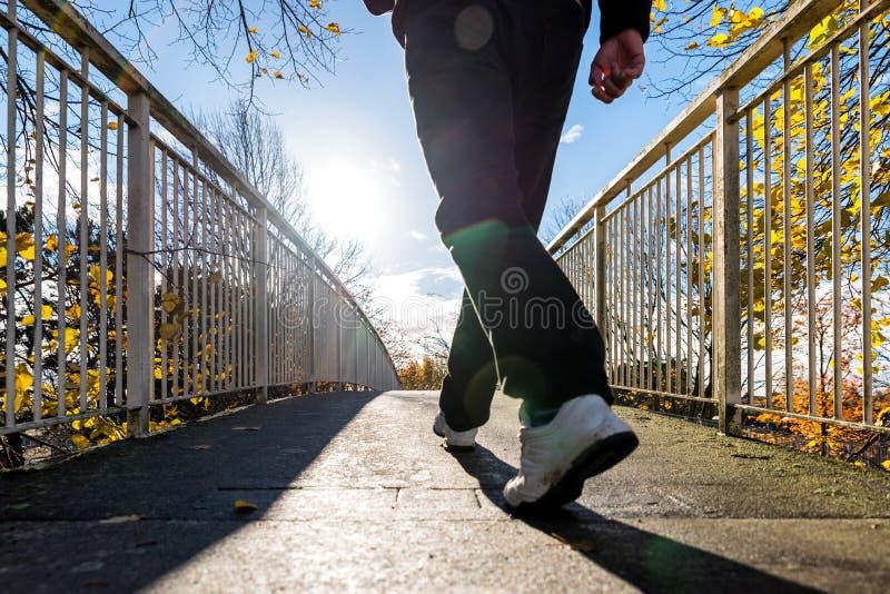 Φωτεινή ηλιόλουστη άποψη πρωινού του ατόμου που περπατά στη για τους πεζούς γέφυρα το βρετανικό φθινόπωρο στοκ εικόνες