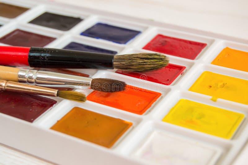 Φωτεινή κινηματογράφηση σε πρώτο πλάνο χρωμάτων watercolor σε ένα κιβώτιο με τις βούρτσες στοκ εικόνες με δικαίωμα ελεύθερης χρήσης