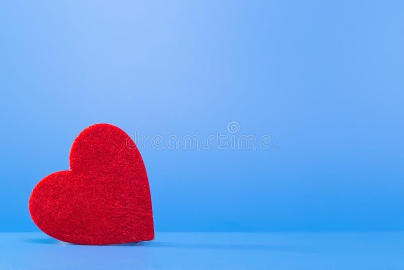 Φωτεινή κόκκινη καρδιά σε ένα μπλε υπόβαθρο στην αριστερή γωνία στοκ φωτογραφίες με δικαίωμα ελεύθερης χρήσης