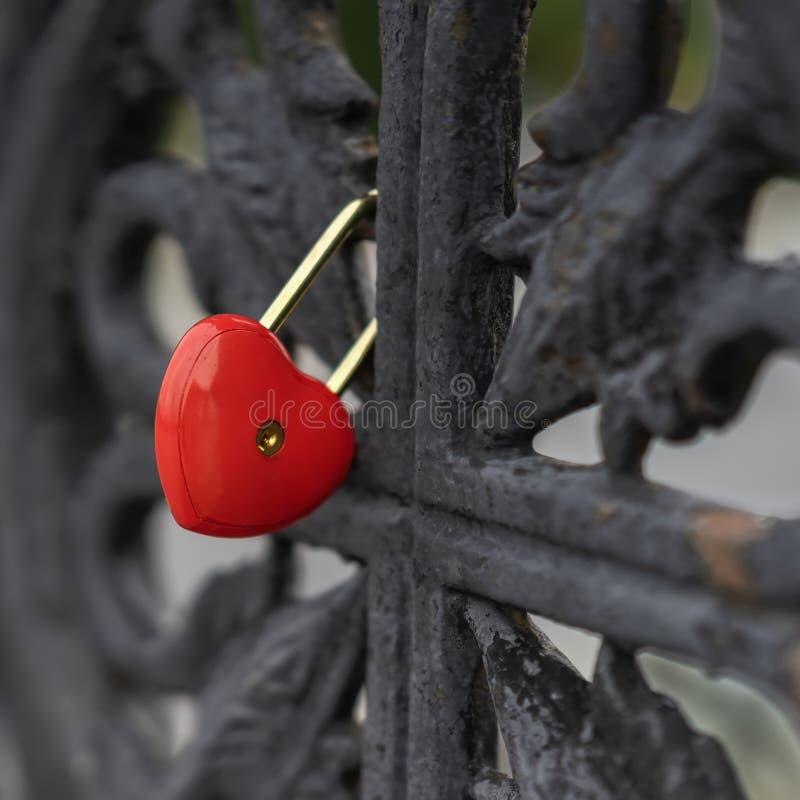 Φωτεινή κόκκινη κλειδαριά με μορφή μιας καρδιάς σε ένα μαύρο παλαιό κιγκλίδωμα της γέφυρας, σύμβολο αγάπης στοκ εικόνες