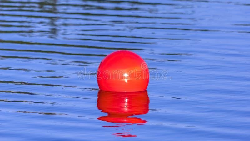 Φωτεινή κόκκινη σφαίρα που επιπλέει στην ήρεμη λίμνη Oquirrh στοκ εικόνες