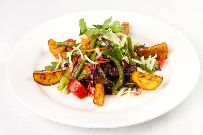 Φωτεινή σαλάτα των υγιών προϊόντων που ντύνονται με τη σάλτσα στο στρογγυλό pla στοκ εικόνες