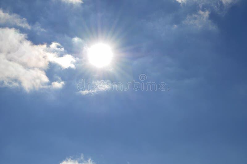 Φωτεινός ήλιος ενάντια σε έναν φωτεινό μπλε ουρανό με τα άσπρα χνουδωτά σύννεφα στοκ εικόνες