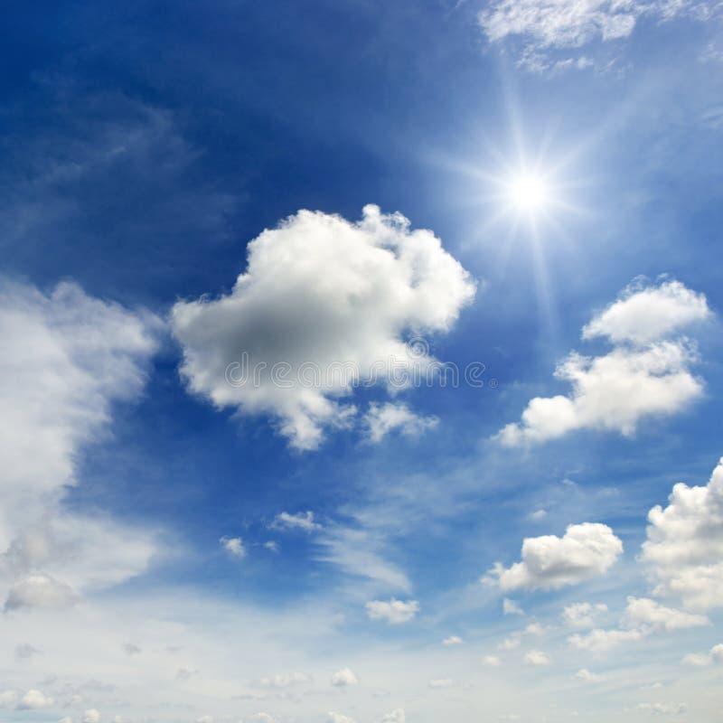 Φωτεινός ήλιος και άσπρα σύννεφα στο υπόβαθρο ενός μπλε ουρανού στοκ φωτογραφίες