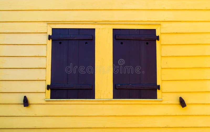 Φωτεινός κίτρινος τοίχος με τα μαύρα παραθυρόφυλλα στοκ φωτογραφία με δικαίωμα ελεύθερης χρήσης