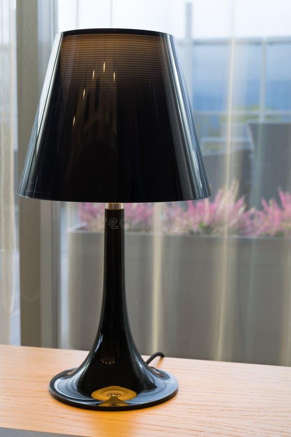 Φωτεινός λαμπτήρας με έναν λαμπτήρα πατωμάτων στο windowsill, το διαφανές Tulle και την άποψη σχετικά με τη θάλασσα, λουλούδι ερε στοκ εικόνες
