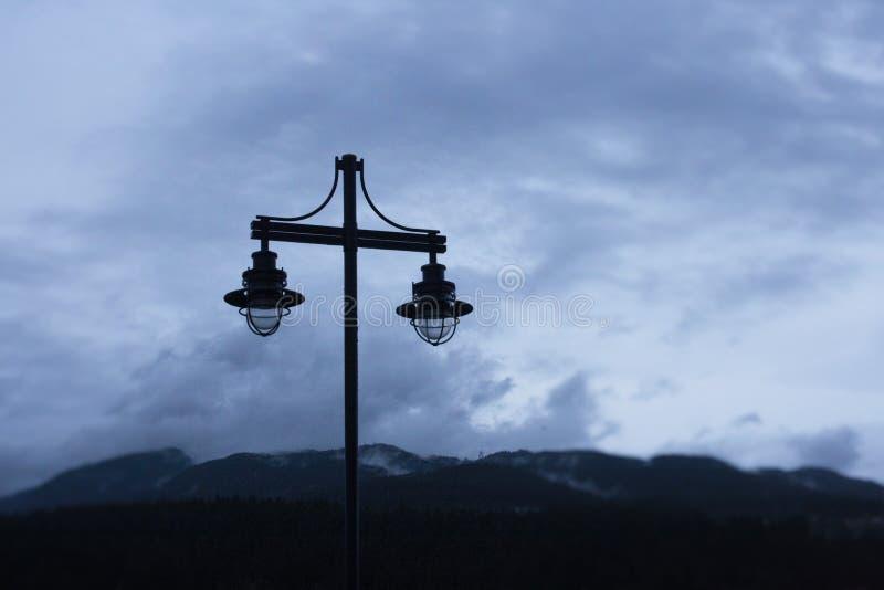 Φωτεινός σηματοδότης με το υπόβαθρο βουνών και ουρανού στοκ φωτογραφία