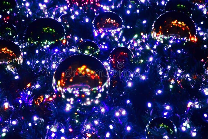 Φωτεινό εορταστικό χριστουγεννιάτικο δέντρο που διακοσμούνται με τις μεγάλες φωτεινές σφαίρες και μια γιρλάντα, κατώτατη άποψη τη στοκ φωτογραφίες