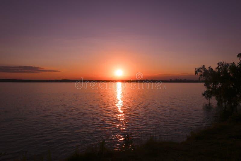 Φωτεινό ηλιοβασίλεμα πέρα από τη λίμνη Κυματισμοί στο νερό στοκ φωτογραφία με δικαίωμα ελεύθερης χρήσης