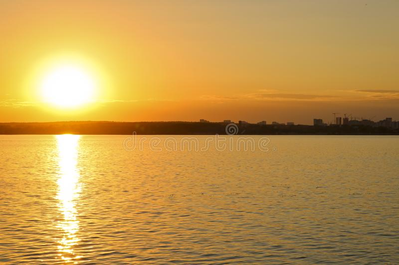 Φωτεινό ηλιοβασίλεμα πέρα από τη λίμνη Κυματισμοί στο νερό Ο ουρανός είναι πορτοκαλής στοκ εικόνες