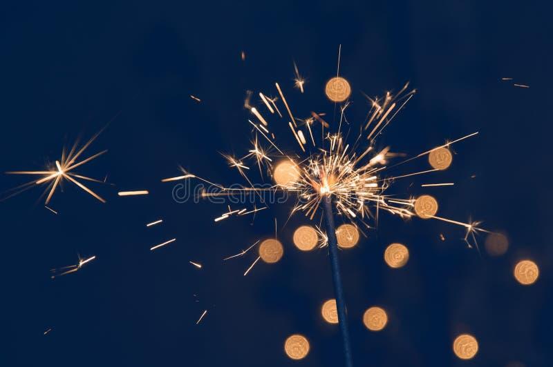 Φωτεινό κάψιμο sparkler με τους πετώντας σπινθήρες Σκούρο μπλε υπόβαθρο με τα θολωμένα φω'τα της γιρλάντας Χριστουγέννων στοκ εικόνες