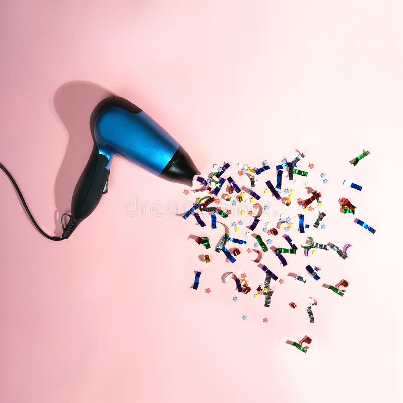 Φωτεινό κομφετί που πετά από το στεγνωτήρα τρίχας στο ρόδινο υπόβαθρο κρητιδογραφιών Νέα έννοια κομμάτων χειμερινών διακοπών έτου στοκ φωτογραφία με δικαίωμα ελεύθερης χρήσης