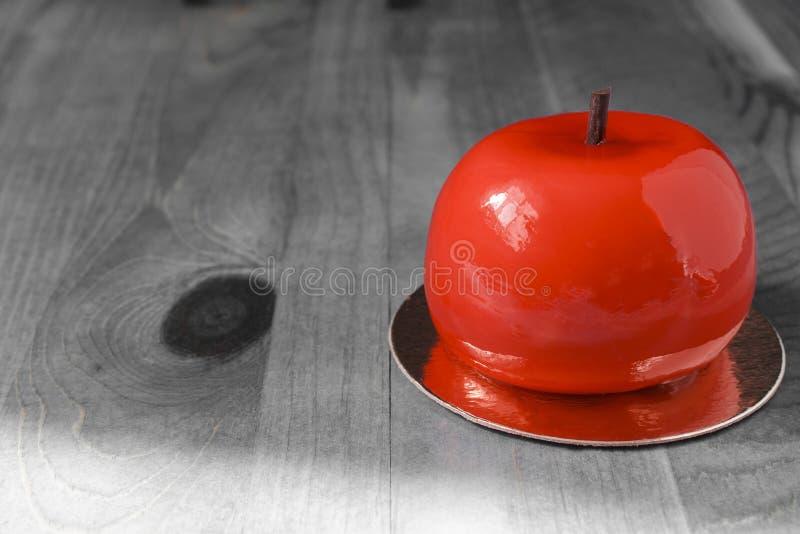 Φωτεινό κόκκινο κέικ υπό μορφή Apple σε μια γραπτή κινηματογράφηση σε πρώτο πλάνο υποβάθρου στοκ φωτογραφία με δικαίωμα ελεύθερης χρήσης