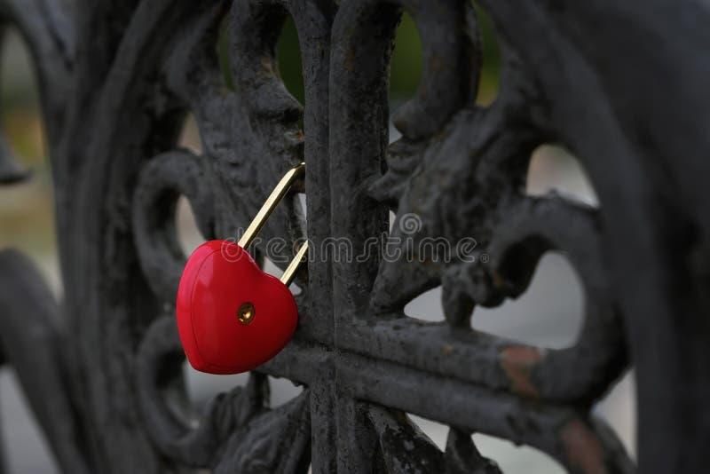 Φωτεινό κόκκινο κλειδωμένο λουκέτο με μορφή μιας καρδιάς σε ένα μαύρο παλαιό κιγκλίδωμα της γέφυρας, σύμβολο αγάπης στοκ εικόνες