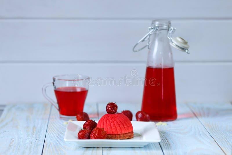 Φωτεινό κόκκινο mousse κέικ που διακοσμείται με τις φράουλες στο φλυτζάνι και το μπουκάλι υποβάθρου με compote φραουλών στοκ φωτογραφίες