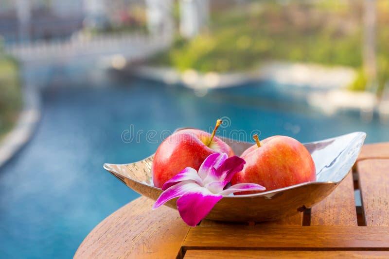 Φωτεινό μήλο με τη ορχιδέα στο πιάτο στον πίνακα στοκ φωτογραφία με δικαίωμα ελεύθερης χρήσης