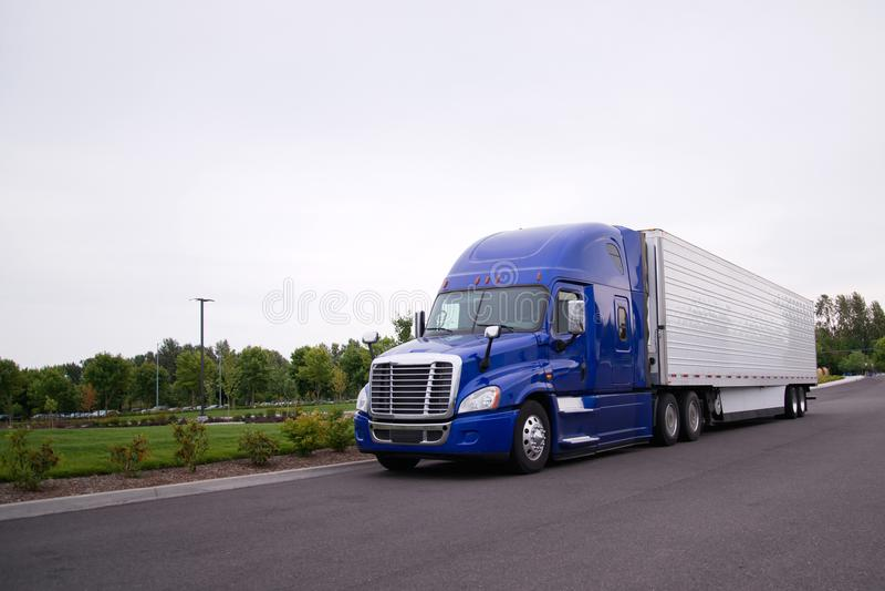 Φωτεινό μπλε μεγάλο ημι φορτηγό εγκαταστάσεων γεώτρησης με το τρέξιμο σημαιοφόρων στο δρόμο στοκ εικόνα με δικαίωμα ελεύθερης χρήσης
