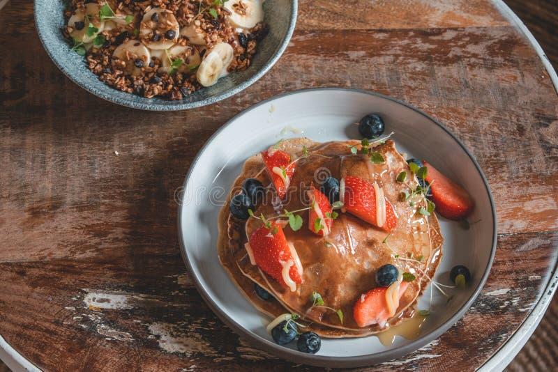 Φωτεινό πιάτο με αμερικανικές τηγανίτες τις υγιείς θερινών προγευμάτων με τα μούρα και ένα κύπελλο δύναμης φιαγμένο από φυσικό γι στοκ εικόνα με δικαίωμα ελεύθερης χρήσης