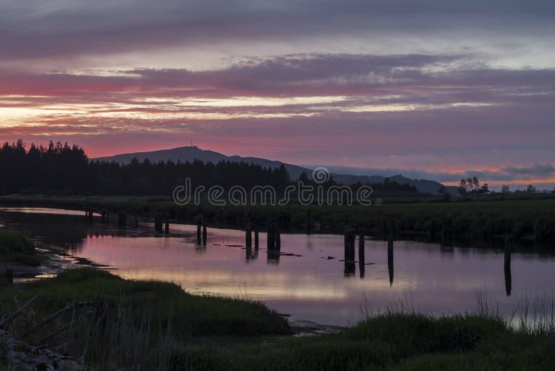 Φωτεινό πολύχρωμο ηλιοβασίλεμα να λάμπει πάνω από το νερό του ποταμού στοκ φωτογραφίες με δικαίωμα ελεύθερης χρήσης