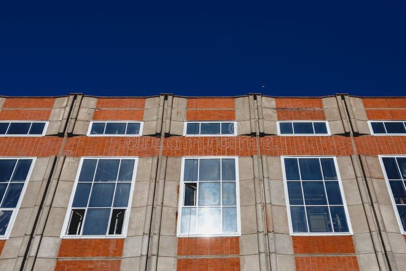 Φωτεινό πορτοκαλί κτήριο σε ένα υπόβαθρο του φωτεινού μπλε ουρανού στοκ φωτογραφία