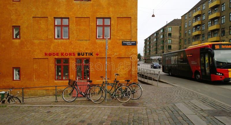 Φωτεινό σπίτι, το ποδήλατο και ο δρόμος με ένα κινούμενο λεωφορείο στην Κοπεγχάγη στοκ εικόνες