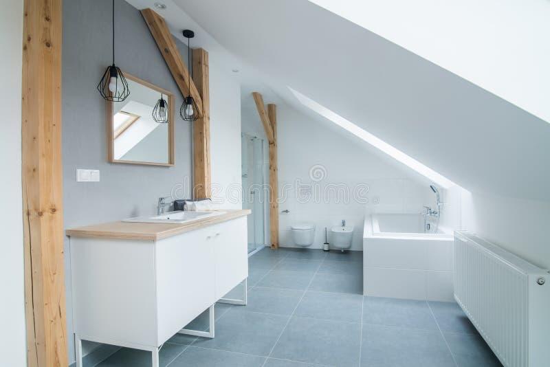 Φωτεινό σύγχρονο λουτρό με τους γκρίζους τοίχους, τον καθρέφτη και την μπανιέρα στοκ φωτογραφία