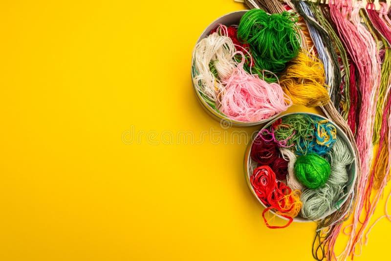 Φωτεινό χρωματισμένο νήμα για το πλέξιμο σε ένα κιβώτιο σε ένα κίτρινο υπόβαθρο στοκ εικόνα