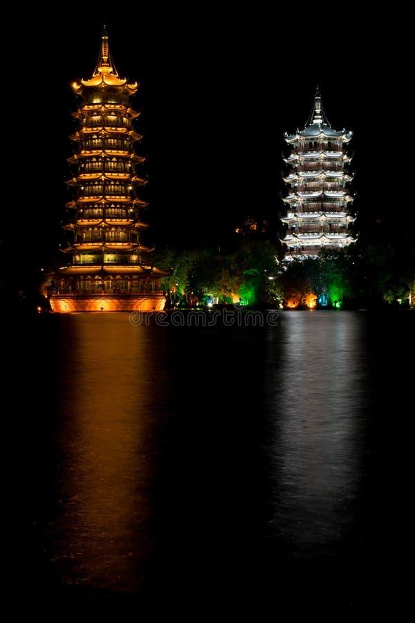 Φωτισμένες παγόδες που απεικονίζουν στο νερό τη νύχτα στοκ εικόνες
