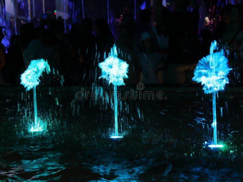 Φωτισμένη πηγή το βράδυ στο πάρκο ένα υπόβαθρο στοκ εικόνα με δικαίωμα ελεύθερης χρήσης