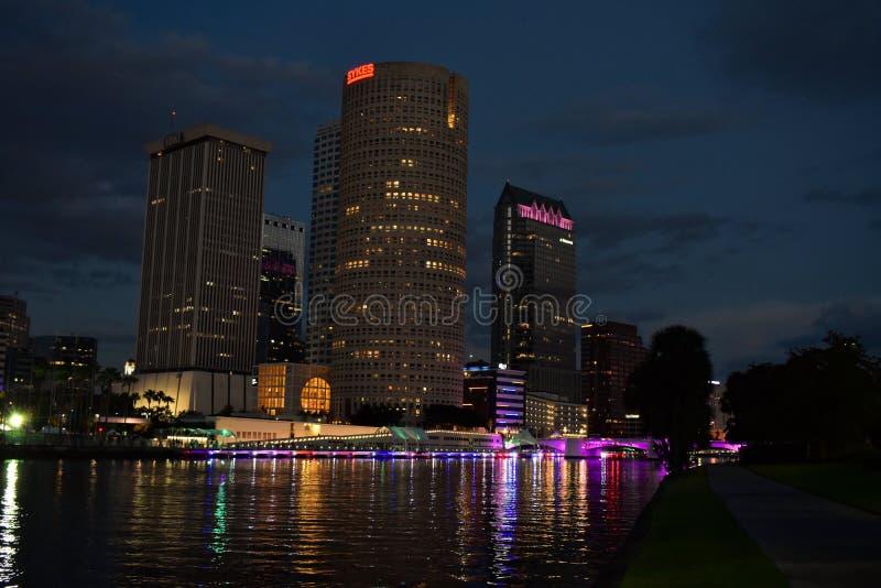 Φωτισμένη πορφυρή γέφυρα πέρα από τον ποταμό στην πόλη ενάντια στον ουρανό στοκ φωτογραφίες