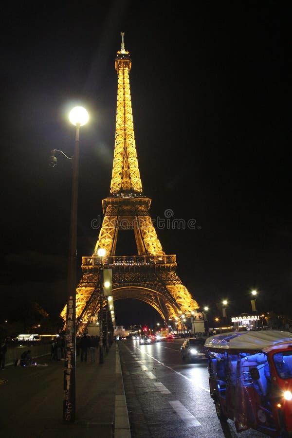 Φωτισμένος πύργος Eifel τη νύχτα με τα αυτοκίνητα στην οδό στοκ εικόνες