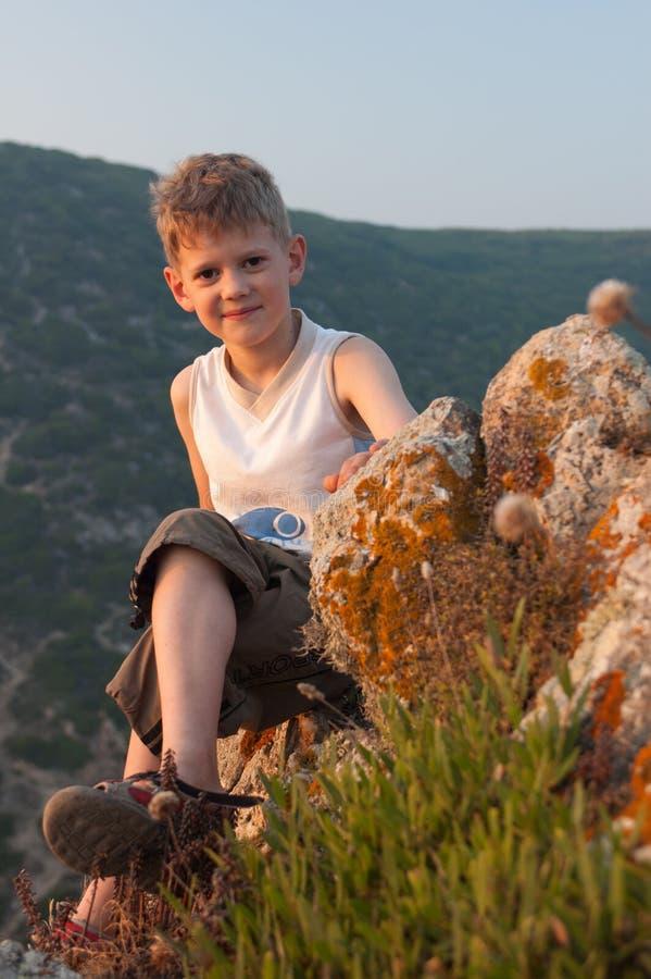 Φωτισμένο από το θερμό φως του ήλιου ηλιοβασιλέματος, το αγόρι κάθεται στην άκρη ενός απότομου βράχου στοκ εικόνα