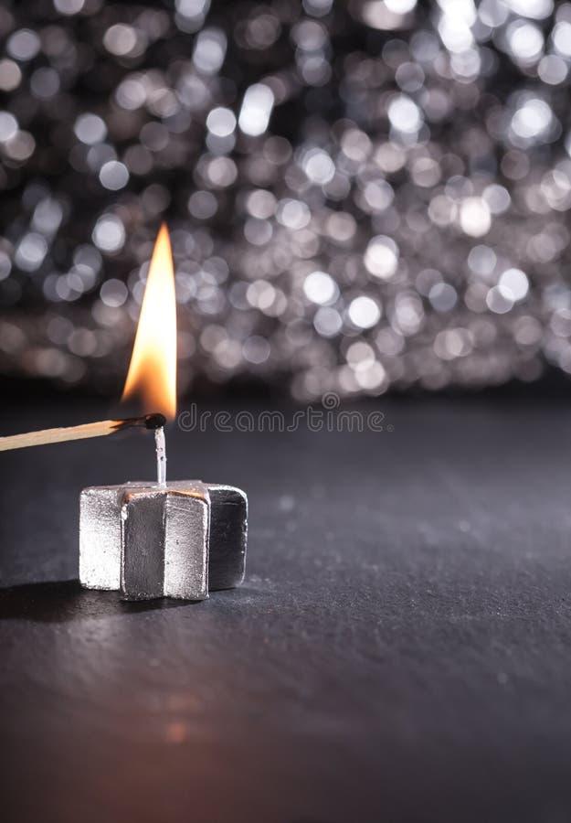 Φωτισμός ενός ασημένιου κεριού με μια αντιστοιχία στοκ φωτογραφία με δικαίωμα ελεύθερης χρήσης