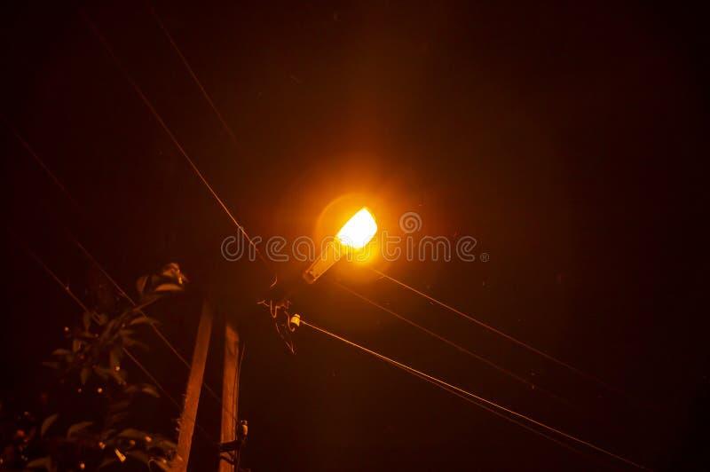 Φωτισμός φαναριών νύχτας σε έναν πόλο ηλεκτροφόρων καλωδίων στοκ εικόνα