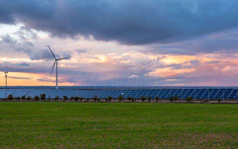 Φωτοβολταϊκές και εγκαταστάσεις αέρα στο ηλιοβασίλεμα στοκ εικόνα με δικαίωμα ελεύθερης χρήσης