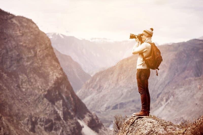 Φωτογράφος ή ταξιδιώτης στο μεγάλο βράχο ενάντια στα βουνά στοκ φωτογραφία