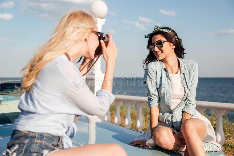 Φωτογράφος γυναικών που παίρνει τις εικόνες του ευτυχούς όμορφου κοριτσιού το καλοκαίρι στοκ εικόνα