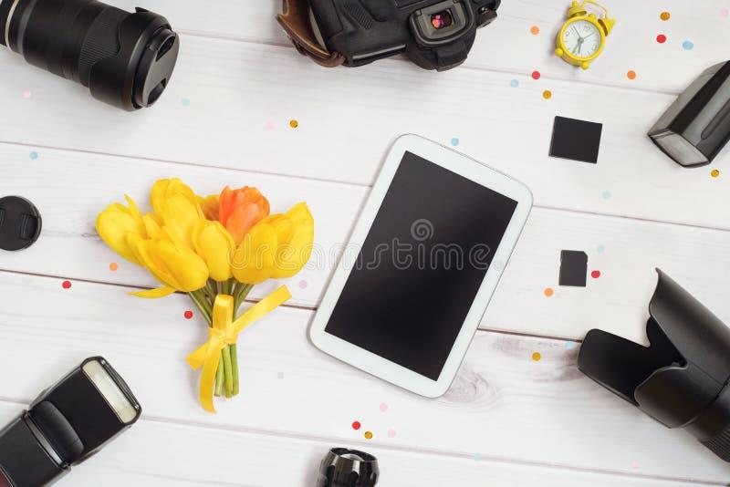 Φωτογράφος εξαρτημάτων: κάμερα, φακός, λάμψη, κάρτα μνήμης, ξυπνητήρι, ταμπλέτα και μια ανθοδέσμη των τουλιπών σε έναν ξύλινο πίν στοκ φωτογραφία με δικαίωμα ελεύθερης χρήσης