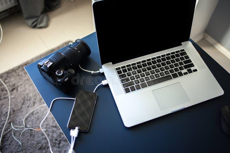 Φωτογράφος και σχεδιαστής εργασιακών χώρων, lap-top με τη κάμερα και smartphone στον πίνακα στοκ φωτογραφία