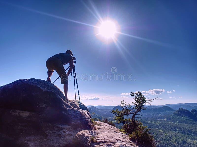 Φωτογράφος με φωτογραφίες από φωτογραφικές μηχανές ενώ στέκεται στην κορυφή στοκ εικόνα