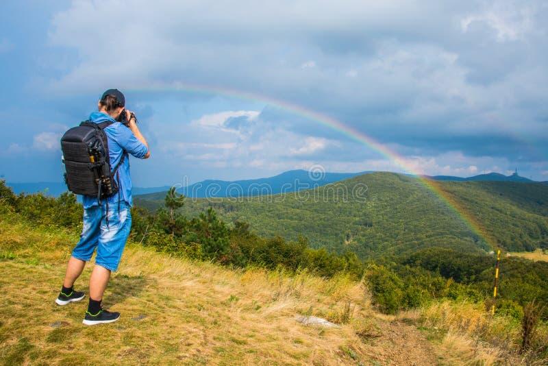 Φωτογράφος που παίρνει μια φωτογραφία ενός ουράνιου τόξου στην απόσταση στοκ εικόνα