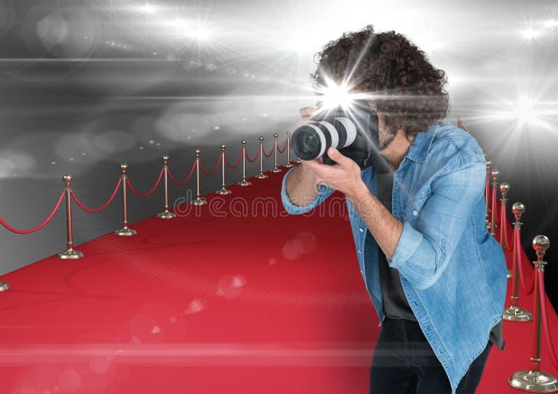 φωτογράφος που παίρνει μια φωτογραφία με τη λάμψη στο κόκκινο χαλί Καίγεται παντού στοκ φωτογραφία με δικαίωμα ελεύθερης χρήσης