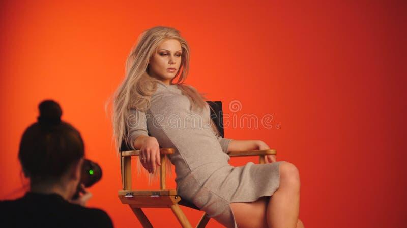 Φωτογράφος που παίρνει τις εικόνες του blondy προκλητικού προτύπου κοριτσιών στο στούντιο στοκ εικόνα με δικαίωμα ελεύθερης χρήσης