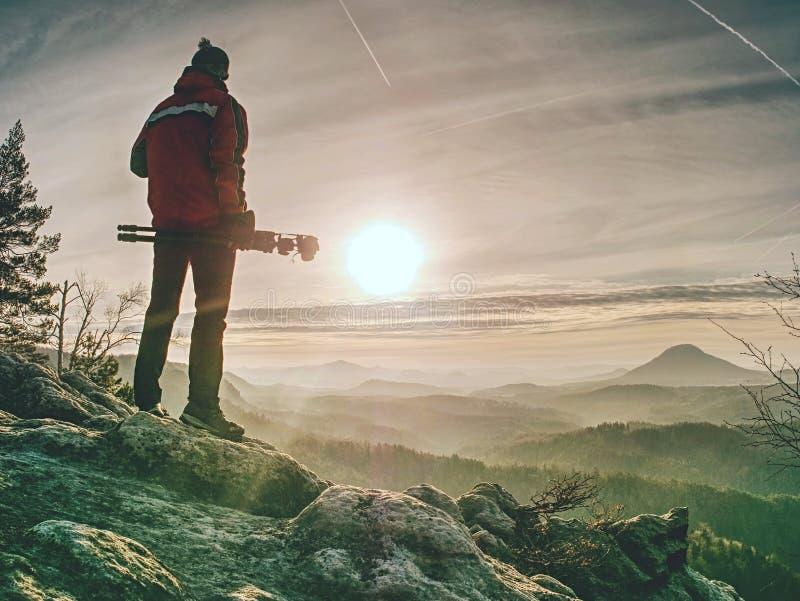 Φωτογράφος στον απότομο βράχο με το τρίποδο διαθέσιμο Φωτογράφος φύσης στοκ εικόνα με δικαίωμα ελεύθερης χρήσης
