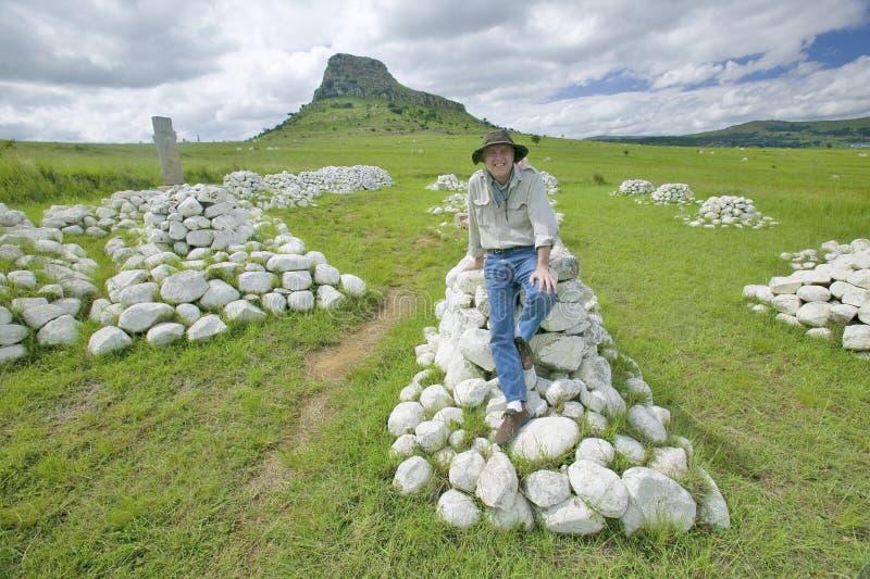 Φωτογράφος Joe Sohm στο λόφο Sandlwana ή Sphinx με τους τάφους στρατιωτών στο πρώτο πλάνο, η σκηνή της ζουλού περιοχής μάχης Angl στοκ φωτογραφίες