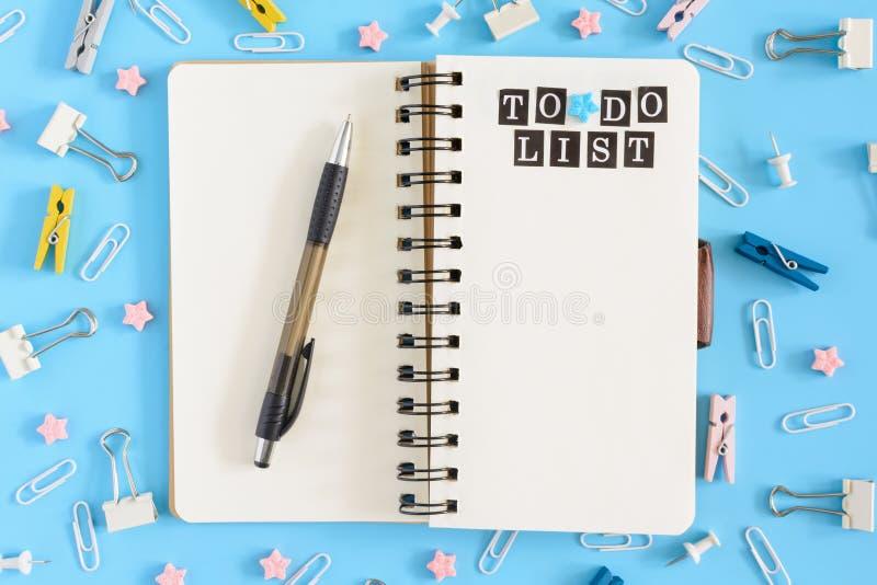Φωτογραφία από την κορυφή με τα διεσπαρμένα χαρτικά Ανοικτό σημειωματάριο στα ελατήρια με τα άσπρα φύλλα Επιγραφή για να κάνει το στοκ εικόνες
