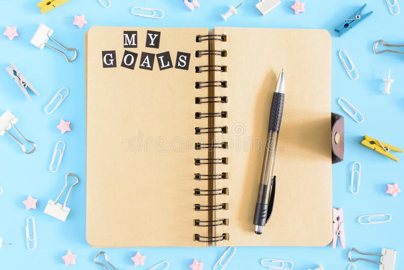 Φωτογραφία από την κορυφή με τα διεσπαρμένα χαρτικά Ανοικτό σημειωματάριο στα ελατήρια με τα καφετιά φύλλα Η επιγραφή οι στόχοι μ στοκ εικόνα με δικαίωμα ελεύθερης χρήσης